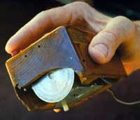 The first computer mouse held by inventor  showing the wheels which directly contact the working surface.