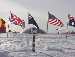 The ceremonial South Pole.  Flags of the  signatories are arrayed around it, and the Pole Station's old dome is in the background.