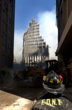 , : A New York City firefighter looks up at what remains of the South Tower.