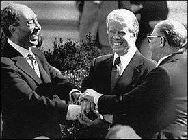 (left),  (center), and  (right) shake hands in celebration of the success of the Camp David Accords