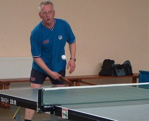 Regional competition level table tennis, showing table, net, and player getting ready to return the ball with a winning backhand topspin stroke.