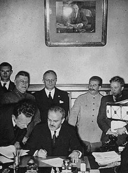 Molotov signs the German-Soviet non-aggression pact. Behind him are Ribbentrop and Stalin.